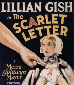 Lillian Gish in the Scarlet Letter movie poster. In the background a young woman with a scarlet A on her chest. In the foreground a much larger male hand pointing at her.